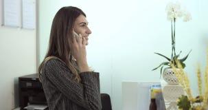 Hjälp för ung kvinna talar på mobiltelefonen bredvid mottagandeskrivbordet lager videofilmer