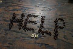 Hjälp mig som är skriftlig i kaffe- och lekstycken royaltyfri bild