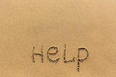 Hjälp - ord som dras på sandstranden Abstrakt begrepp Royaltyfri Foto