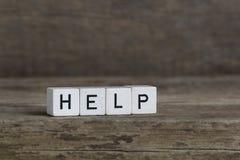 Hjälp som är skriftlig i kuber royaltyfria foton