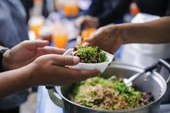 Hjälpa att lätta hunger från människovännen av folk i samhälle: dela för begreppsmat royaltyfria foton