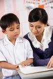 Hjälpande deltagare för lärare som fungerar på skrivbordet Royaltyfri Fotografi
