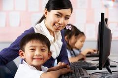 Hjälpande deltagare för lärare under datorgrupp Royaltyfria Bilder