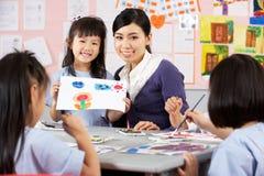 Hjälpande deltagare för lärare under konstgrupp Arkivfoton