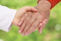 hjälpande sjuksköterskapensionär Arkivfoto