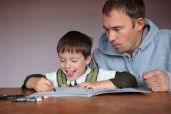 Hjälpande son för fader som gör läxa Arkivfoton