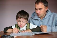 Hjälpande son för fader som gör läxa Fotografering för Bildbyråer