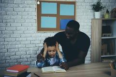 Hjälper den enkla fadern för afrikanska amerikanen den trötta sonen arkivfoto