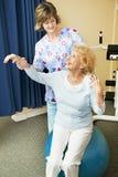 hjälper den fysiska höga terapeutkvinnan Arkivfoton