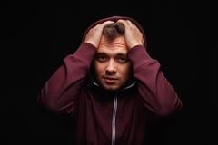 Hjälplös student som rymmer hans huvud i chock Förvirrad grabb på en svart bakgrund Man med mentala problem Chockbegrepp Royaltyfri Foto