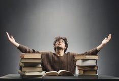 Hjälplöst sammanträde för ung man på skrivbordet mycket av böcker Arkivbild