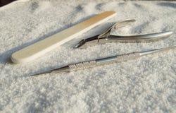 Hjälpmedel av en manikyruppsättning på vit bakgrund, begrepp av omsorg av spikar och nagelband arkivbild