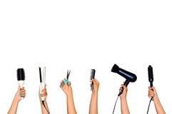 Hjälpmedel för att utforma hårinnehavet i händer som isoleras på vita lodisar royaltyfri fotografi