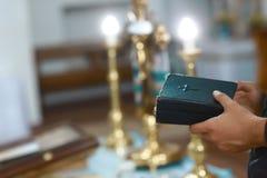 Hjälpmedel för behandla som ett barn dop bönbok i händerna av prästen Catholicism, begreppet av kristendomen royaltyfri foto
