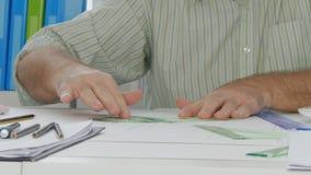 Hjälpmedel för Businesspersonbruksteckning som gör tekniskt projekt på papperet lager videofilmer