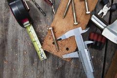 Hjälpmedel för Diy hemarbete som arbetar på den wood tabellen med wood plankamutteravskummar Arkivfoton