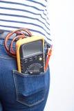Hjälpmedel för elektriker i bakficka av jeans som är sliten vid en kvinna multimeter Royaltyfri Bild