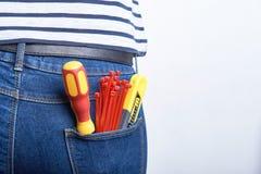 Hjälpmedel för elektriker i bakficka av jeans som är sliten vid en kvinna Skruvmejsel, skarp kniv och vinandeband Royaltyfria Bilder