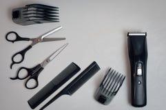Hjälpmedel för en frisyr: sax, hårkammar och en beskärare Royaltyfri Foto