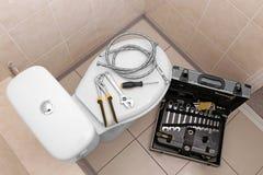 Hjälpmedel för rörmokare` s på toalett arkivfoto