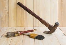 Hjälpmedel-, hammare- och målarfärgborste på wood bakgrund Fotografering för Bildbyråer