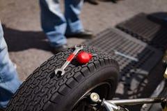 Hjälpmedel ligger överst av ett hjul för springa bil Royaltyfria Bilder
