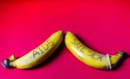 HJÄLPMEDEL och säkra könsbestämmer begrepp av kondomen på bananen för bög Royaltyfri Foto