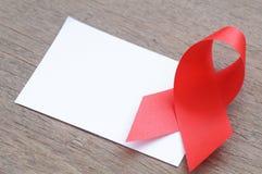 HJÄLPMEDEL, rött band och vitbok Royaltyfria Bilder
