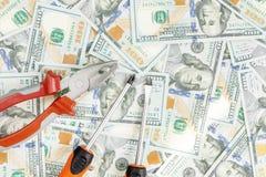 Hjälpmedel som ligger över 100 dollar sedelbakgrund Plattång och skruvmejsel mot USA-pengar Korrigering, fixande och förbättring  Royaltyfri Foto