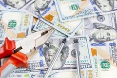 Hjälpmedel som ligger över 100 dollar sedelbakgrund Plattång och skruvmejsel mot USA-pengar Korrigering, justering och förbättrin Royaltyfri Foto