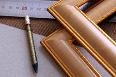 Hjälpmedelenhetsramar, ramar, för bilder, foto, linjal, blyertspenna på beige bakgrund arkivfoton