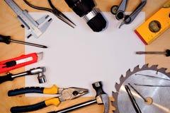 Hjälpmedelram på träbakgrund, feriefaderdag Populärt låssmedhjälpmedel för kreativitet - en hammare, plattång, skruvmejslar, såg arkivbilder