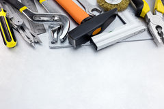 Hjälpmedeluppsättning av hammare, linjaler, skiftnyckel och plattång på skrapad metall Arkivbild