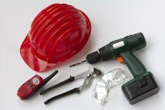 Hjälpmedeluppsättning med säkerhetshjälmen, drillborren, skiftnycklar, walkie-talkie och säkerhetsexponeringsglas Royaltyfri Foto
