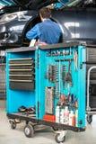 Hjälpmedelvagn med den manliga mekanikern Repairing Car royaltyfri fotografi