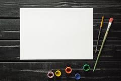 Hjälpmedlen av konstnären, borstarna, målarfärgerna och kanfasen är inte mörk träbakgrund arkivbild