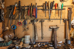 Hjälpmedlen på väggen och tabellen som håller hammare, skiftnycklar, cirkelskruvnycklar, hammare, plattång, skruvmejslar, skiftny Arkivfoto