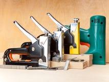 Hjälpmedlet - elektriska häftapparater och manuellt mekaniskt - för reparationsarbete i huset och på möblemang fotografering för bildbyråer
