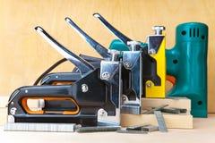 Hjälpmedlet - elektriska häftapparater och manuellt mekaniskt. Industriell stilleben arkivbild