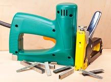 Hjälpmedlet - elektriska häftapparater och manuellt mekaniskt. Slut upp arkivfoton