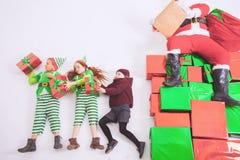 Hjälpredor för jultomten` som s arbetar på nordpolen Honom som läser önskalistan Arkivbilder