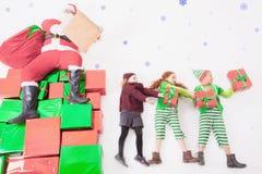 Hjälpredor för jultomten` som s arbetar på nordpolen Honom som läser önskalistan Arkivfoto