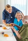 Hj?lpsam doktor eller sjuksk?terskan Serving Senior Adult kopplar ihop sm?rg?sar arkivbilder