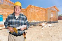 Hjälpsam manlig leverantör med husplan som framme bär den hårda hatten av Ne Arkivbild
