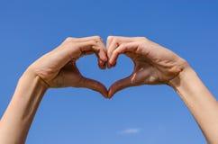 Hjärta av fingrarna med den blåa himlen Arkivfoton