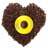 Hjärta av kaffebönor med den gula koppen Fotografering för Bildbyråer