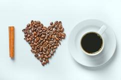 Hjärta av kaffebönor på en vit bakgrund med kanel Arkivfoton