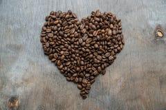 Hjärta av kaffebönor på träbakgrund Arkivfoton