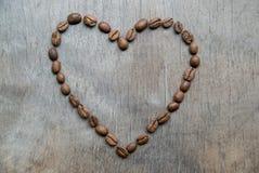 Hjärta av kaffebönor på träbakgrund Arkivbilder