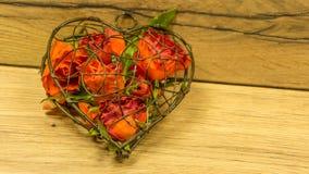 Hjärta av metall och rosor arkivbild